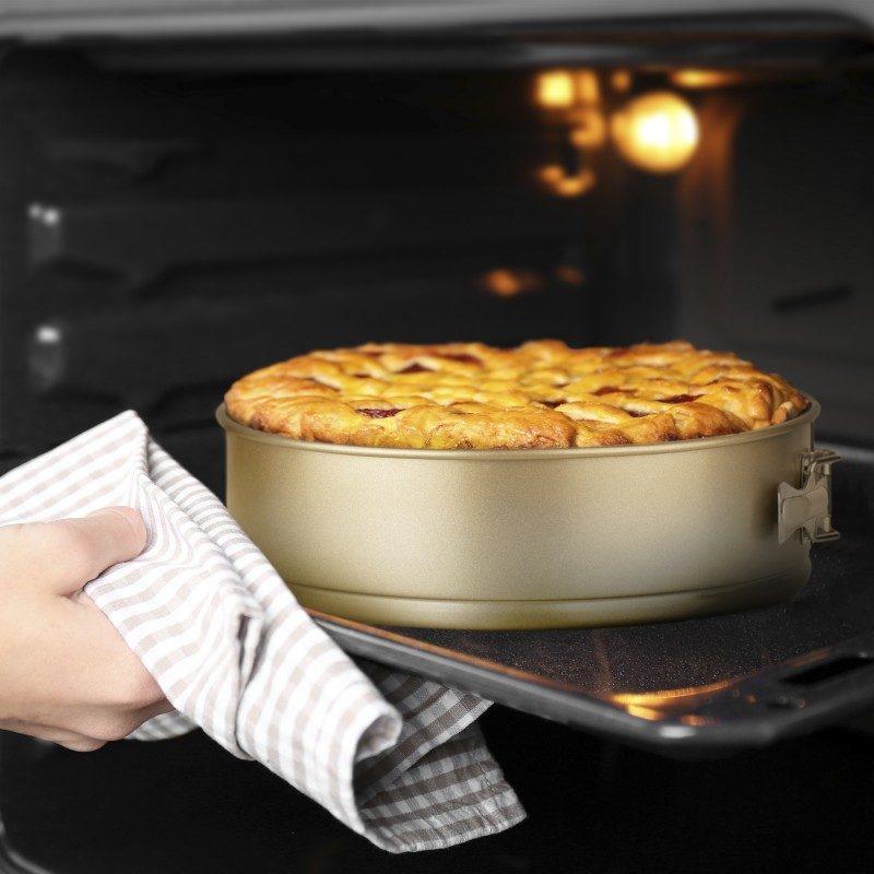 Okrogli pekač Rosmarino Baker Golden 28 cm iz visokokakovostnega karbonskega jekla in modernega videza v zlati barvi bo vaš novi nepogrešljiv pripomoček pri peki. Neoprijemljiv premaz z učinkom vročega kamna omogoča edinstven pristop k peki, saj boste lahko uporabili nič ali minimalno količino maščob. Hrana se tako ne bo oprijela pekača, njeno odstranjevanje bo enostavno, brez uporabe kuhinjskih pripomočkov. Pekač ima snemljiv obod, ki se ga enostavno odstrani z zaklopko iz nerjavečega jekla, ki preprečuje uhajanje tekočine med peko. Zaradi sestave iz karbonskega jekla je pekač odporen tudi na visoke temperature, do 240 °C, primeren za hrambo v hladilniku in pomivanje v pomivalnem stroju. Idealen pripomoček za peko tort, pit in drugega okroglega peciva.