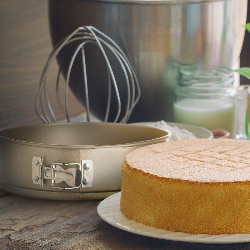Okrogli pekač Rosmarino Baker Golden 24 cm iz visokokakovostnega karbonskega jekla in modernega videza v zlati barvi bo vaš novi nepogrešljiv pripomoček pri peki. Neoprijemljiv premaz z učinkom vročega kamna omogoča edinstven pristop k peki, saj boste lahko uporabili nič ali minimalno količino maščob. Hrana se tako ne bo oprijela pekača, njeno odstranjevanje bo enostavno, brez uporabe kuhinjskih pripomočkov. Pekač ima snemljiv obod, ki se ga enostavno odstrani z zaklopko iz nerjavečega jekla, ki preprečuje uhajanje tekočine med peko. Zaradi sestave iz karbonskega jekla je pekač odporen tudi na visoke temperature, do 240 °C, primeren za hrambo v hladilniku in pomivanje v pomivalnem stroju. Idealen pripomoček za peko tort, pit in drugega okroglega peciva.