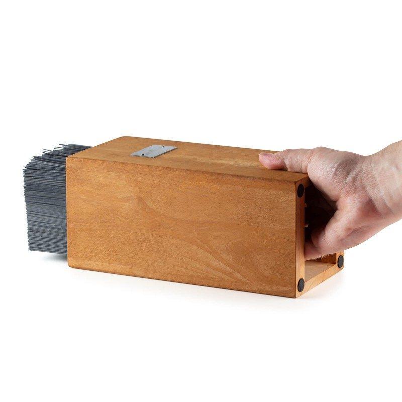 Moderno zasnovano leseno stojalo za nože Rosmarino Blacksmith's je izjemno stabilno in je priročna rešitev za varno odlaganje nožev, različnih velikosti. Noži so v stojalu vedno pospravljeni, a hkrati vedno pri roki. V notranjosti lesenega ogrodja je nastavek iz drobnih polipropilenskih palčk, ki se odmaknejo rezilu noža in ga ne poškodujejo, hkrati pa ga trdno oprimejo in mu zagotavljajo pokončno lego. Posamezni noži lahko tako stojijo v stojalu kjer koli, ne glede na velikost noža. Navadni, običajni leseni bloki, imajo narejene tulce, ki ustrezajo točno določenim vrstam noža, kar pomeni zamudno pospravljanje in sortiranje, pri stojalu Blacksmith's pa bodo vaši noži vedno pregledno zloženi. Stojalo je izdelano iz naravi prijaznega kavčukovega lesa, z insertom iz PP plastike.