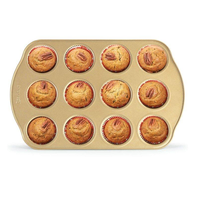 Pekač za 12 muffinov Rosmarino Baker Golden iz visokokakovostnega karbonskega jekla in modernega videza v zlati barvi bo vaš novi nepogrešljiv pripomoček pri peki. Neoprijemljiv premaz z učinkom vročega kamna omogoča edinstven pristop k peki, saj boste lahko uporabili nič ali minimalno količino maščob. Hrana se tako ne bo oprijela pekača, njeno odstranjevanje bo enostavno, brez uporabe kuhinjskih pripomočkov. Zaradi sestave iz karbonskega jekla je pekač odporen tudi na visoke temperature, do 240 °C, primeren za hrambo v hladilniku in pomivanje v pomivalnem stroju. Idealen pripomoček za peko muffinov, mini tortic in slanega kiša.