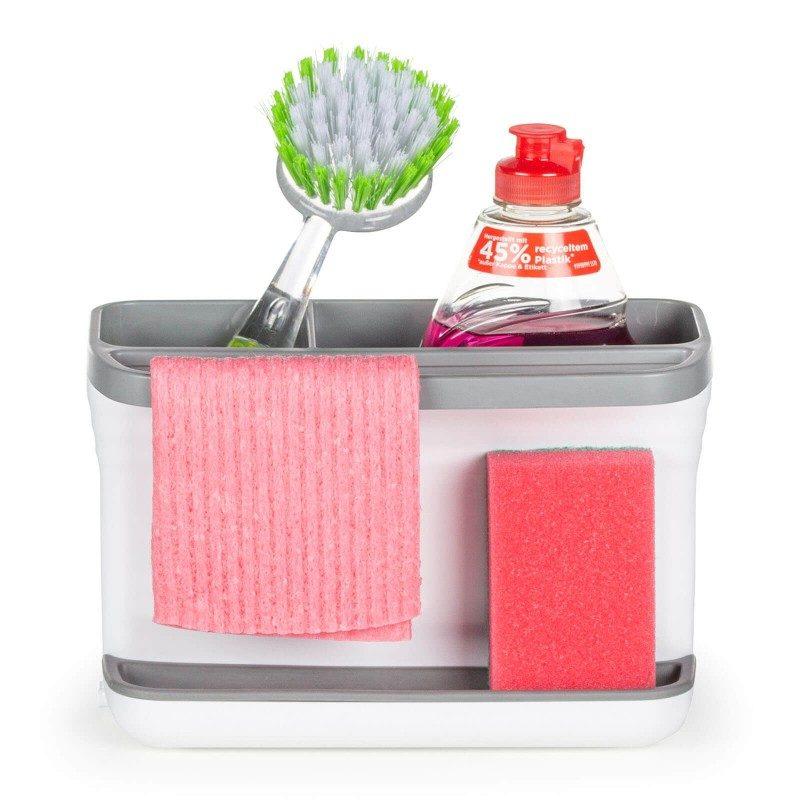 Majhen, a izjemno priročen kuhinjski organizator za hrambo čistilnih pripomočkov. Večji predel je kot nalašč za varno hrambo čistilnega detergenta, v manjšega pa udobno pospravite čistilno krtačko. Silikonska podloga za čistilno gobico bo vpila vso odvečno vodo, tako nikoli več ne boste imeli težav z odvečnim kapljanjem in mokrim odlagalnim koritom. Priročno držalo je idealno za obešanje gobaste krpe ali manjše kuhinjske brisačke. Po končanem odcejanju preprosto dvignete zgornji del organizatorja in odlijete odvečno vodo in tako počistite organizator. Najbolj priročen in enostaven način za hrambo gobic, detergentov in drugih čistilnih pripomočkov - vse v eni posodi in na enem mestu.